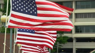 American Flags fly in slow motion in front of a typical small city backdrop