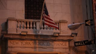 An American Flag flies above an entrance to the NY Stock Exchange at evening