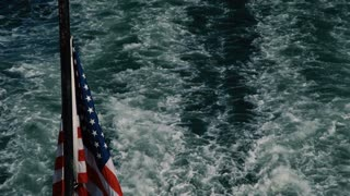 An American Flag hovers over the wake of a boat. (POV from Rear of boat)