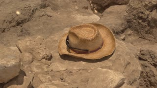 An Archeologists hat rests on an excavation dig site