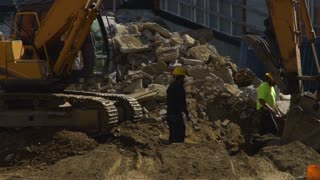 An Excavator scoops dirt and debris near Construction workers