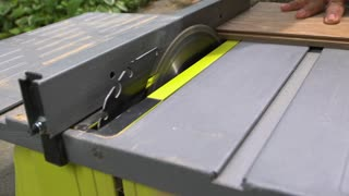 An outdoor table saw trims / cuts a piece of wood