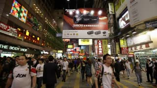 Busy Pedestrians in a ad & light filled shopping center in Hong Kong