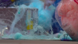 Carnival snacks are prepared behind a web of blue and pink cotton candy