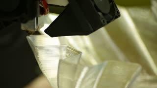 Closeup: A 3d Printer Nozzle lays down the next layer of its construction