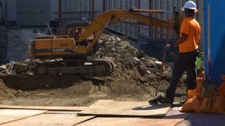 Construction worker with a broom walks in slow motion near Excavator