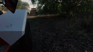 Convoy of ATVs speed through a grove of Trees and a puddle on rocky roads