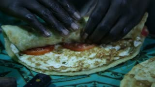 Cook in restaurant in Uganda finishes making & rolling a wrap
