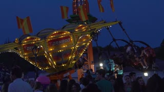 Crowd Gathers around a Spinning Tornado Ride at Night during Carnival