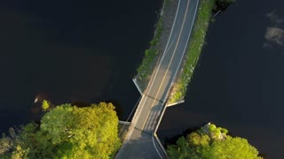 Drone Aerial: Looking straight down on car entering bridge over Lake