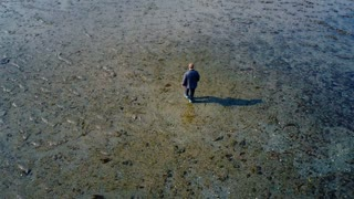 Drone Circles Man and Dog Wading through Shallow Waters