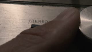 Extreme Closeup: Fingers turn the worn metal dial on an old stereo radio