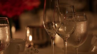 Glasses reflect Candlelight at a fancy dinner table