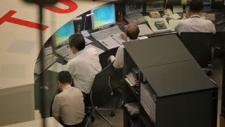 Individuals at workstations during a Calm Day at the Tokyo Stock Exchange
