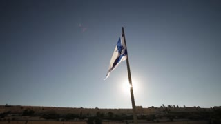 Israeli Flag and sun-flare over the old city of Jerusalem