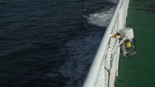 Looking down off the side of a moving Ferry, safety light on the railing