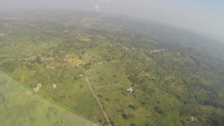 Looking out the window of a prop plane flying over Ugandan countryside