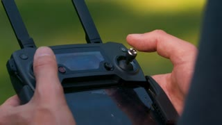 Man uses his thumbs on small joysticks to operate a drone via controller