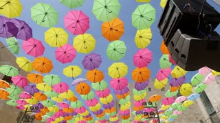 Pan Up on Colorful Umbrellas hung above a Street
