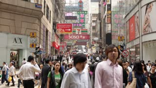 Pedestrians walk through a busy wide alley filled with ads in Hong Kong