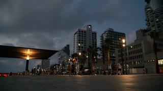 People run and walk along the boardwalk near the beach at Tel-Aviv at Night