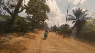 POV: Car with broken windshield follows motorcycle through outskirts of Kampala