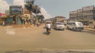 POV: Car with broken windshield travels through traffic in Kampala Uganda