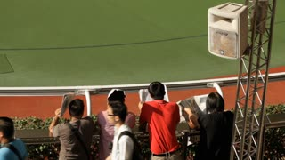 Spectators wait for the next race with newspapers at a Horse Track in Hong Kong