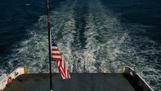 The American Flag flies off the back of a boat and its wake/waves.