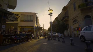 The evening sun casts long shadows on a corner street in Tel Aviv