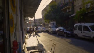 The evening sun casts long shadows on a street in Tel Aviv