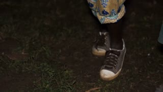 The feet of young boys / children in Uganda dance at night at a Wedding