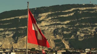 The Swiss Flag flies in front of a mountain in Geneva