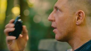 Vaping Man blows smoke in closeup against a nature / green backdrop