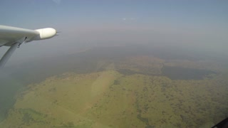 View out the window of small prop plane flying over Uganda fields and farms