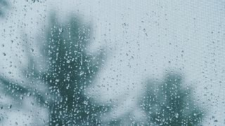 Water droplets drip down a screen window during a heavy thunderstorm
