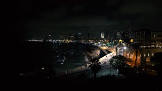 Waves crash along the beach in a wide shot of Tel-Aviv at Night