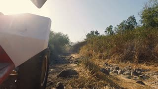 Wheel POV: An ATV climbs over rough terrain on a rocky road
