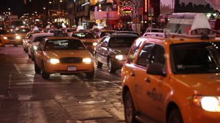 Yellow Taxis and other traffic clog the night streets of NYC near Broadway