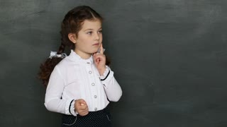 a little girl standing at the blackboard