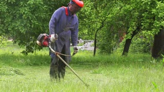 a man mowing grass in the village
