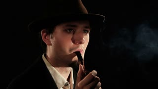 A young man smoking a pipe