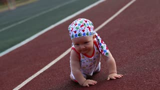 baby boy crawling in the stadium