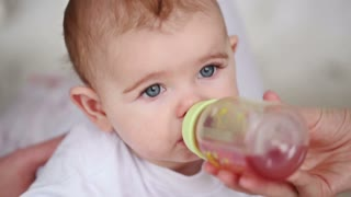 baby drinks juice from a bottle