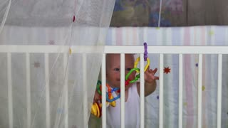 baby learns to stand holding support in the crib