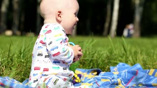 baby playing in the park on a blanket - dolly shot