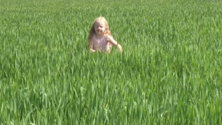 beautiful blonde girl running on the green field