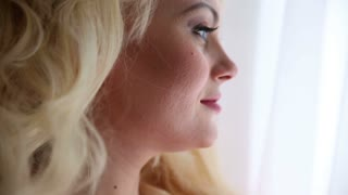 beautiful blonde woman pensively looking out of the window, closeup