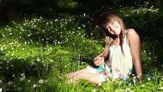 beautiful girl in forest on flowers field