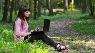 beautiful girl with a laptop in the forest
